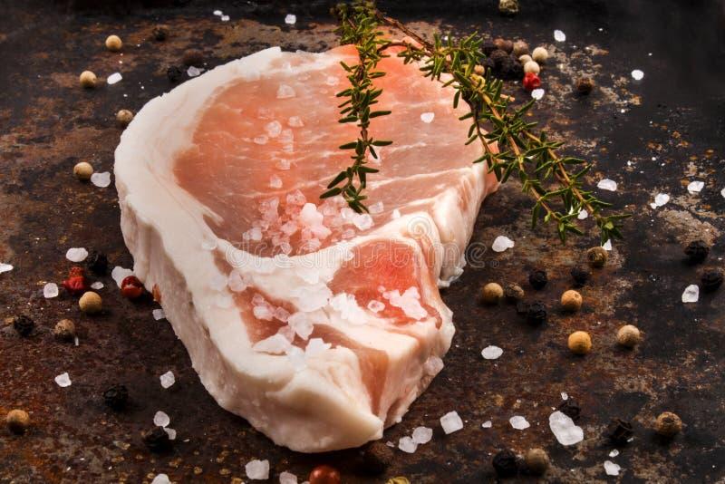 Chuleta de cerdo con tomillo, el grano de pimienta y la sal gruesa en un shee del metal fotografía de archivo libre de regalías