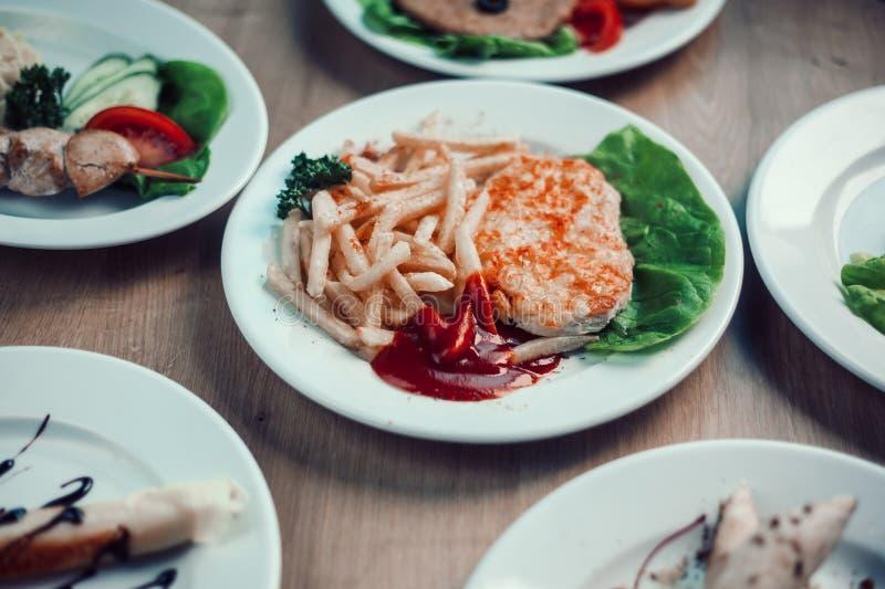 Chuleta de cerdo y patatas fritas en una placa en la mesa de comedor imagenes de archivo