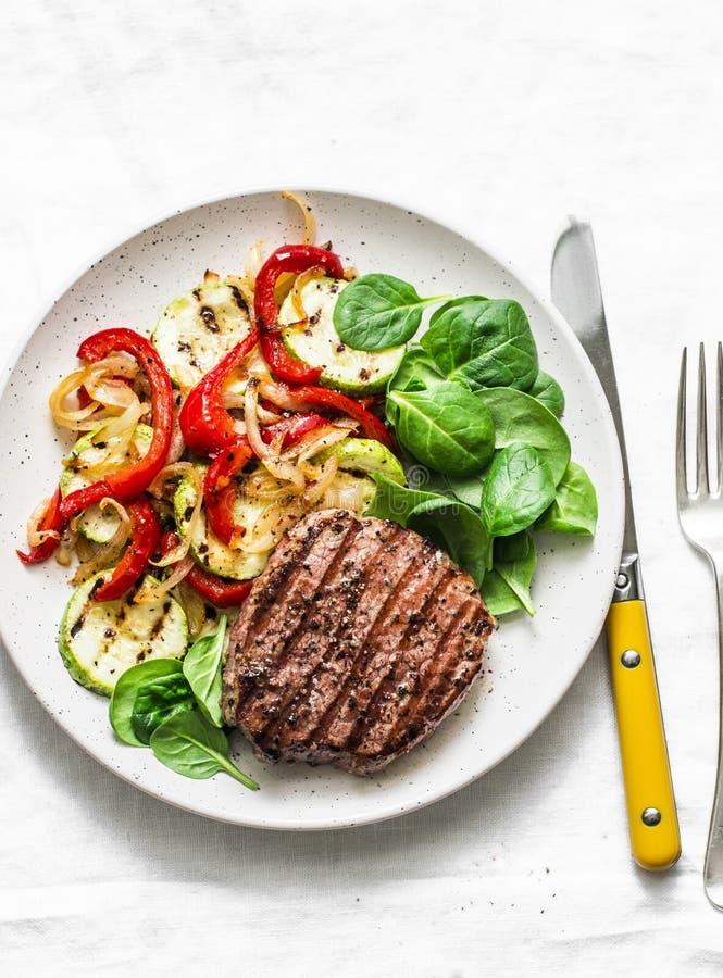 Chuleta y verduras asadas a la parrilla - almuerzo equilibrado sano delicioso en un fondo ligero, visión superior de la carne de  foto de archivo