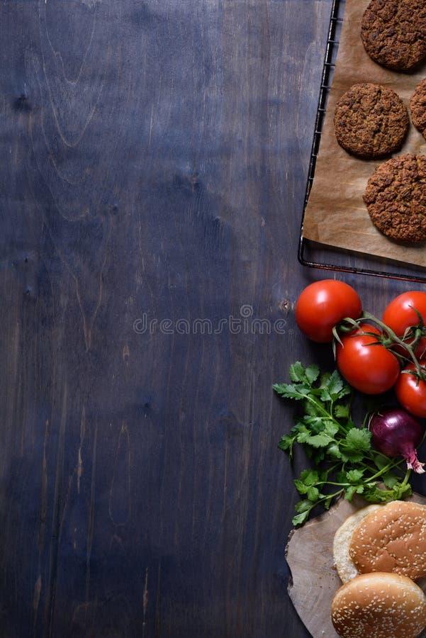 Chuletas asadas a la parrilla del filete de la hamburguesa de la carne de la carne picada con el condimento, los tomates, el pere imágenes de archivo libres de regalías