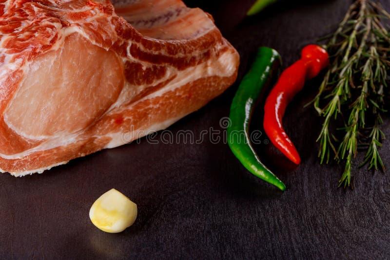 Chuletas de cerdo crudas con las hierbas y las especias en tabla de cortar Aliste para cocinar imágenes de archivo libres de regalías