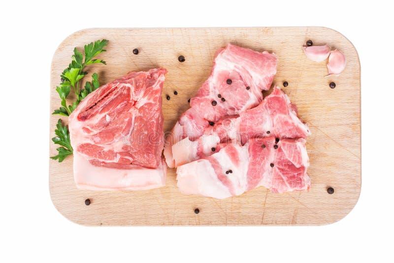 Chuletas de cerdo crudas en tabla de cortar de madera imagen de archivo