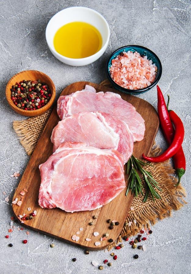 Chuletas de cerdo crudas frescas con las especias y las hierbas fotografía de archivo libre de regalías