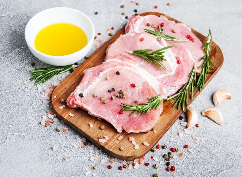 Chuletas de cerdo crudas frescas con las especias y las hierbas foto de archivo