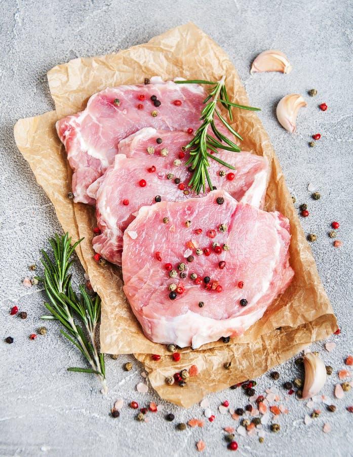 Chuletas de cerdo crudas frescas con las especias y las hierbas imágenes de archivo libres de regalías