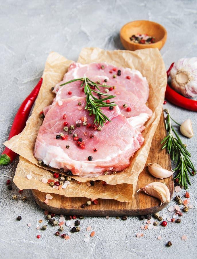 Chuletas de cerdo crudas frescas con las especias y las hierbas foto de archivo libre de regalías