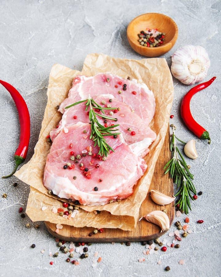 Chuletas de cerdo crudas frescas con las especias y las hierbas fotos de archivo libres de regalías