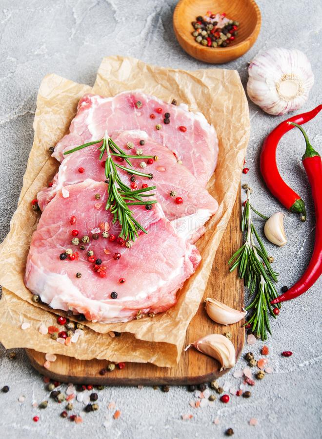 Chuletas de cerdo crudas frescas con las especias y las hierbas imagen de archivo