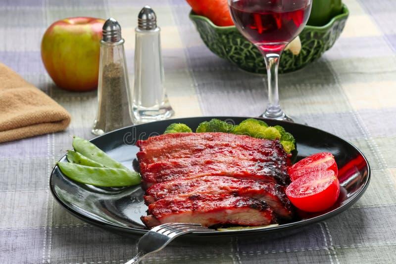Chuletas de cerdo del Bbq en una tabla de cena fotos de archivo
