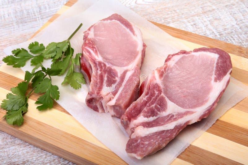 Chuletas de cerdo, especias y albahaca crudas en tabla de cortar Aliste para cocinar fotografía de archivo