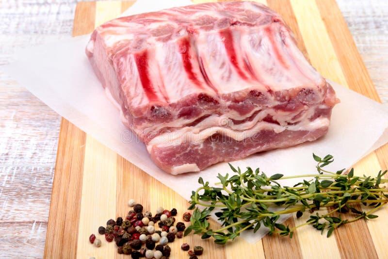Chuletas de cerdo, especias y romero crudos en tabla de cortar Aliste para cocinar imagen de archivo