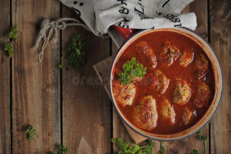 Chuletas de la carne en la salsa de tomate, cocida en un sartén Adornado con perejil en un fondo de madera, colores rústicos del  imágenes de archivo libres de regalías