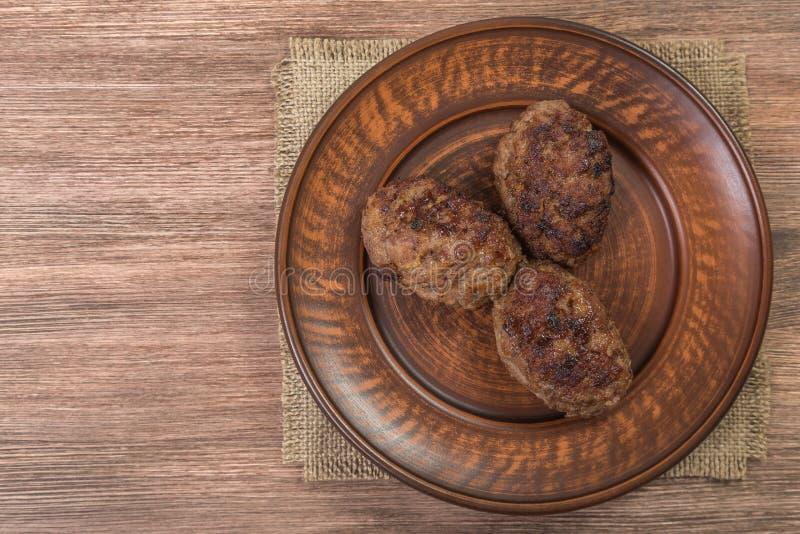 Chuletas hechas en casa de la carne en un plato de cerámica marrón fotografía de archivo