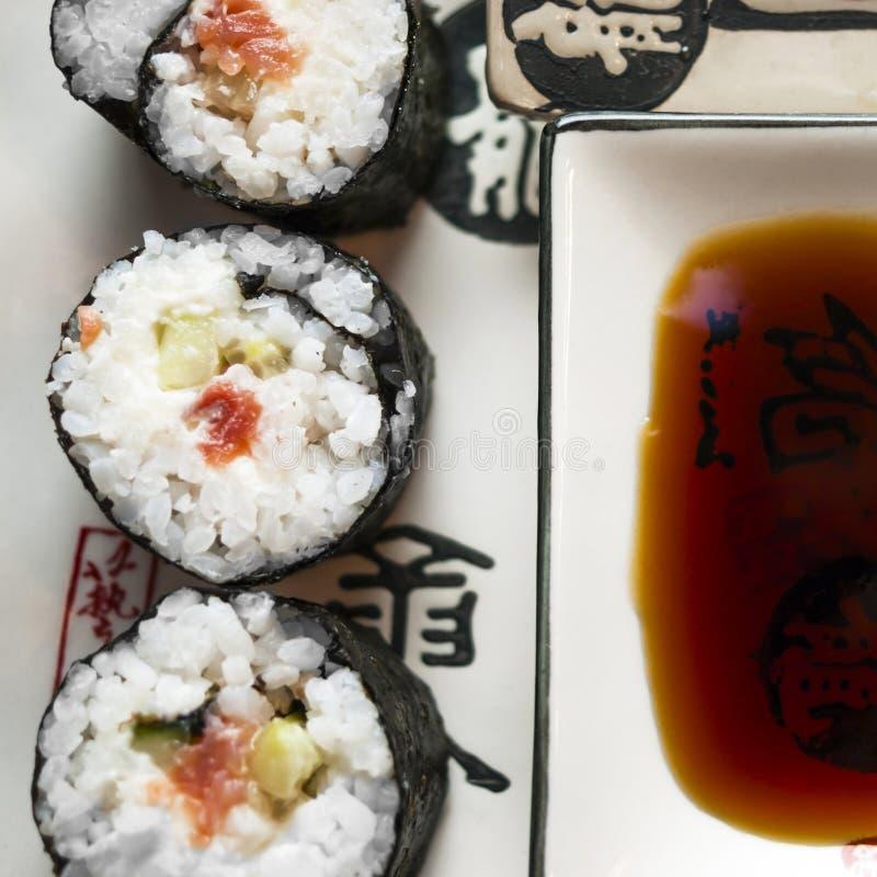 Chumaki sushi Rolls med tonfisk, laxen, ris, gurkan, avokadot och Nori Seaweed på en platta med soya som doppar maträtten och arkivfoto