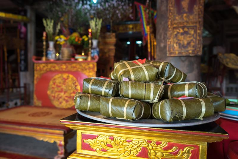 Chung cake on altar in old village communal house. Cooked square glutinous rice cake, Vietnamese lunar new year food.  stock photography
