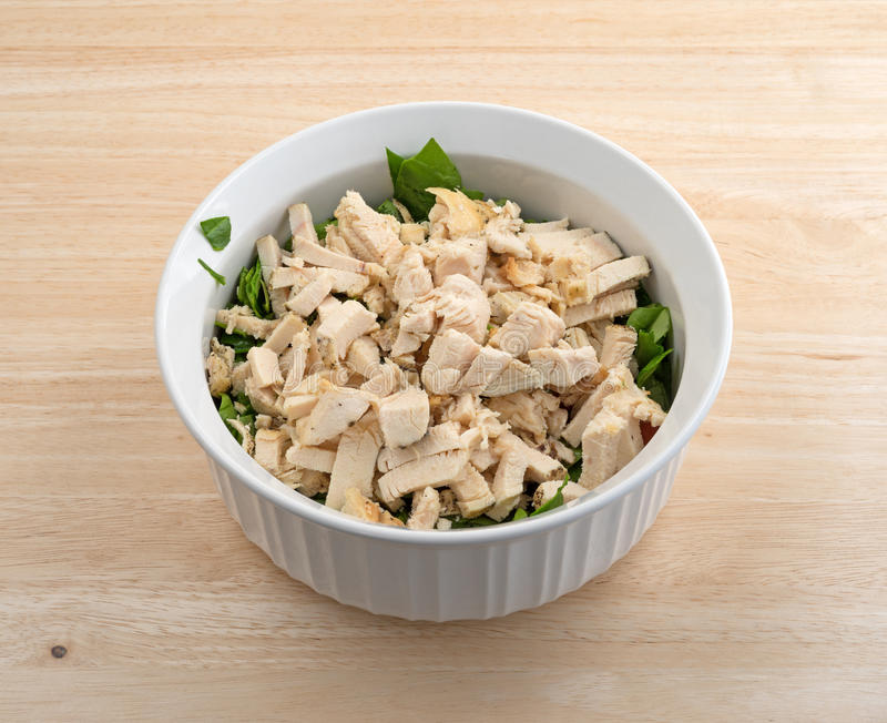 Chunks of chicken breast in a bowl with spinach stock images