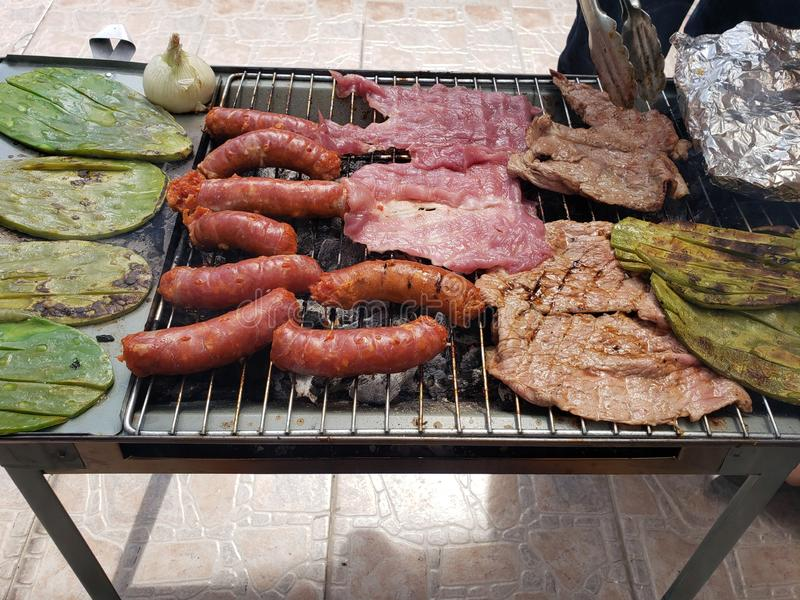 Chunks of chorizo, nopales and grilled meat stock images