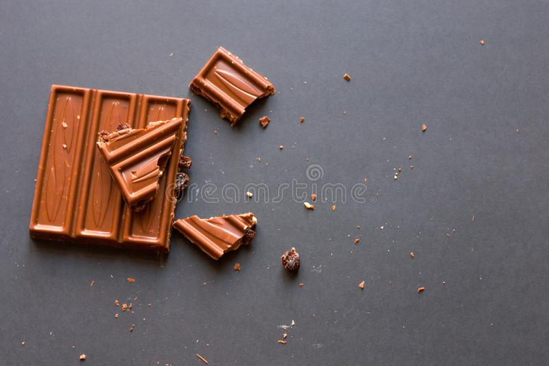 Chunks of milk chocolate with crushed hazelnuts and raisins with alcohol on black background. Confectionery degustation.  royalty free stock photography