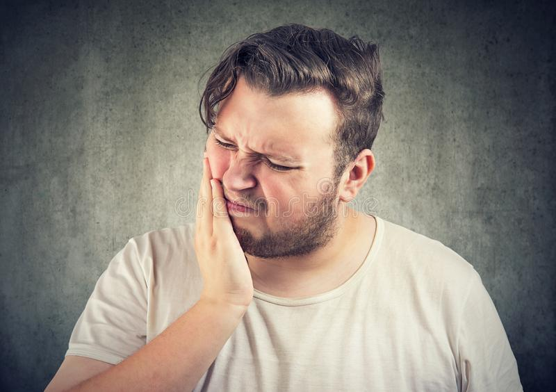 Chunky man having strong toothache. Adult casual man frowning from pain in tooth looking sick and unhappy stock images