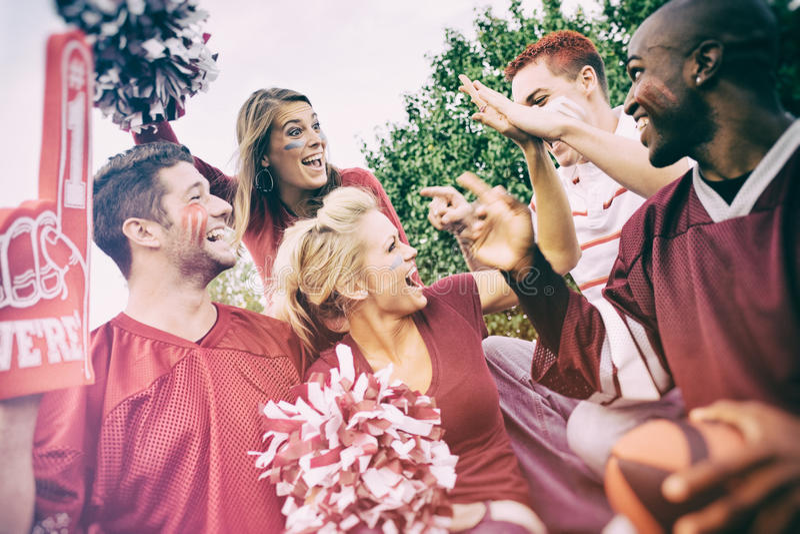 Chupar rueda: Grupo de estudiantes universitarios emocionados para el partido de fútbol imagenes de archivo