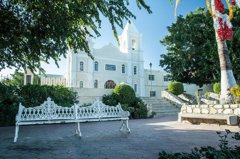 Church adjacent to City Square. Small city square with park bench located adjacent to the Catholic church downtown San Jose Del Cabo in Baja Sur Mexico stock photos