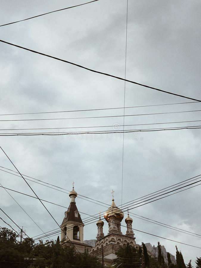 Church against blue sky. Photo of church against blue sky and rocky mountains in Alupka, Crimea. Sky is cut with electric wires of old city stock photography
