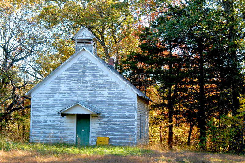 Church in the Backwoods. Old church sits on a countryroad in the Mountains of Arkansas. Whitewash is peeling and sign is on the ground. Fall foilage frames in stock images