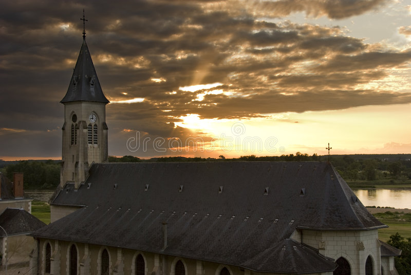Church on a bank. Of Loire river. Sun behind clouds on the background. Next to the castle Chaumont-sur-Loire, Loire Valley, France royalty free stock image
