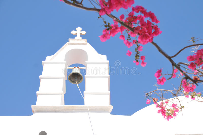Church Bell and pink flowers in Mykonos, Greece royalty free stock photos