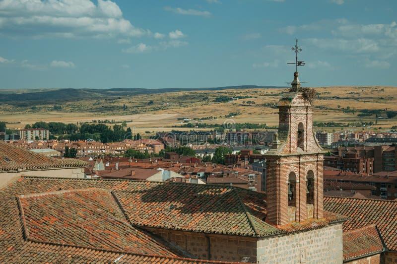 Church bell tower made of bricks amid roofs at Avila royalty free stock photography
