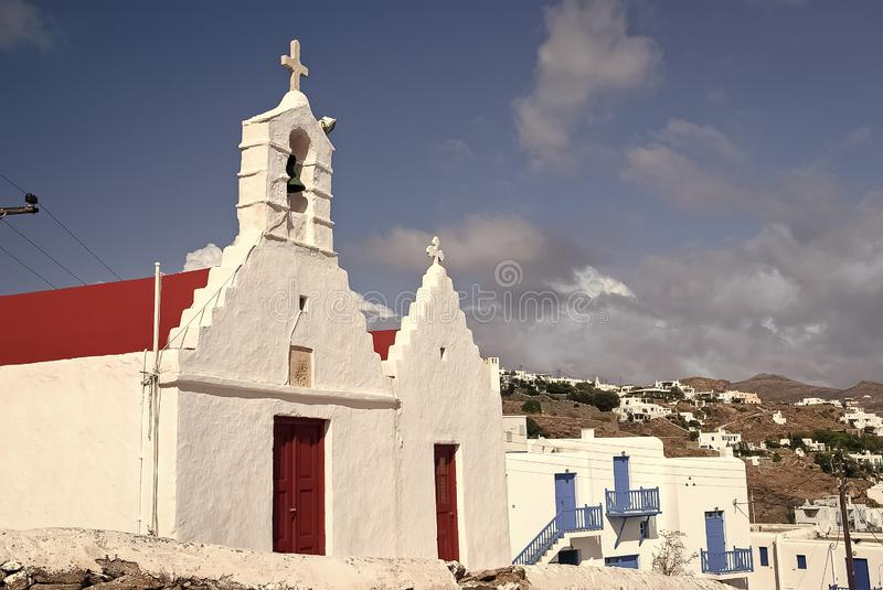 Church with bell tower in Mykonos, Greece. Church building architecture on blue sky. Houses on mountain landscape. Church with bell tower Church building royalty free stock photo