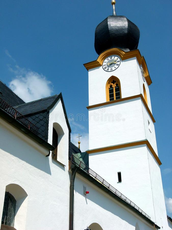 Church with brilliant white facade and black spire in front of blue sky. Newly renovated church, typical german church building style with onion Tower, Church royalty free stock image