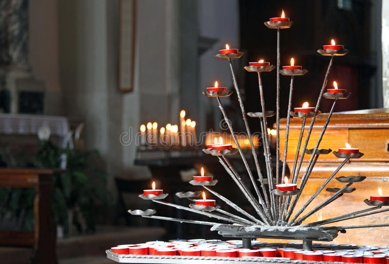 Church with candelabra and lit candles during the prayers of the. Church interior with candelabra and lit candles during the prayers of the faithful royalty free stock photography