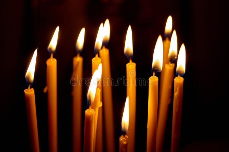 Church candles glowing in the dark create a spiritual atmosphere. Church candles burning in the dark create a spiritual atmosphere. Hope. Prayer. sorrow, faith stock photography