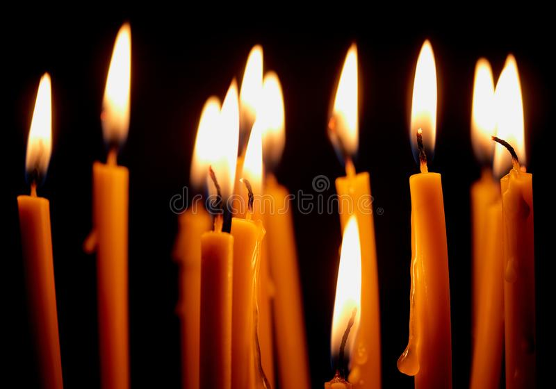 Church candles glowing in the dark create a spiritual atmosphere. Church candles burning in the dark create a spiritual atmosphere. Hope. Prayer. sorrow, faith stock image