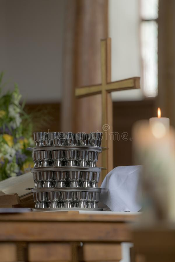Church cross stands on an altar with a communion cup and blurred burning candle stock photography