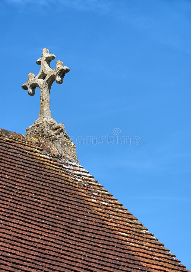 Stone cross on tiled church roof. West Clandon, Surrey. royalty free stock photos