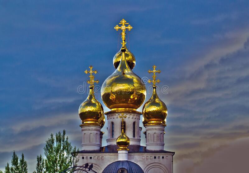 Church crosses and golden domes against a disturbing dark sky royalty free stock photos