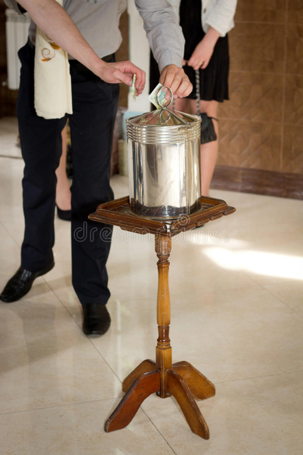 Church - Donation Box. Inserting a banknote into offertory box stock images