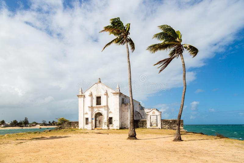 Church and fortress of San Antonio on Mozambique island, with two palm trees on sand. Indian ocean coast, Nampula province. stock image