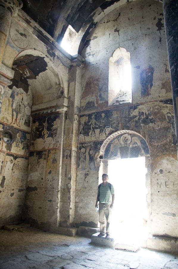 Church frescoes. A male tourist entering the ruins of an ancient ruin of a church with frescoes on the interior walls stock photos