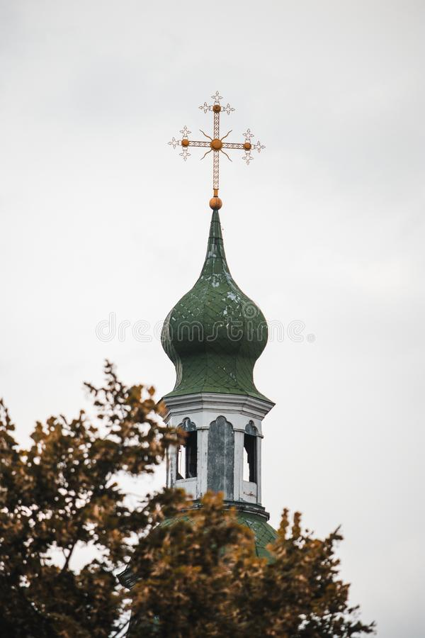 A church with a golden cross towers above the trees stock photo