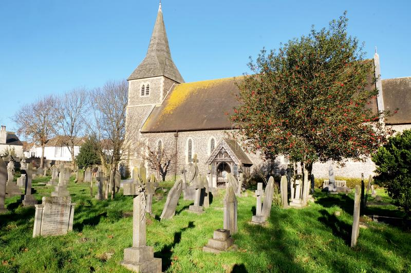 Church and grave yard with holly tree in Hove, East Sussex, United Kingdom. A beautiful old church and grave yard with a holly tree full of red berries in Hove stock photography