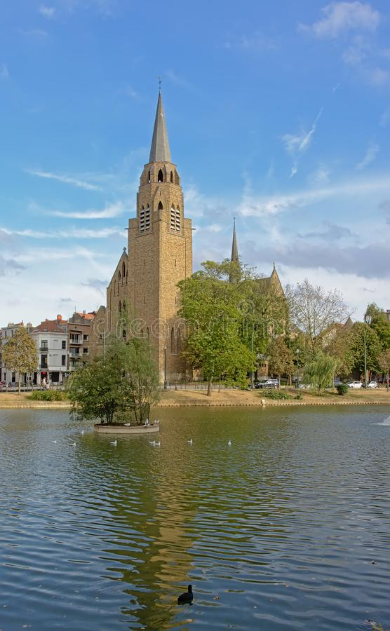 Church of the holy cross, reflecting in the water of Ixelles lakes stock image