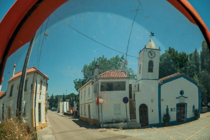 Church and house reflected in a street mirror stock photography