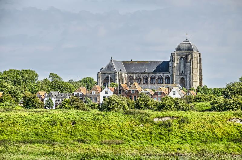 Church and houses in the town of Veere. Massive 15th century gothic church towering above the houses of the town of Veere, The Netherlands, as seen from the royalty free stock image