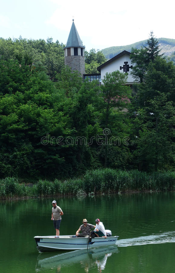 A church with its bell tower and boat on the lake of Castel dell`Alpi royalty free stock photos