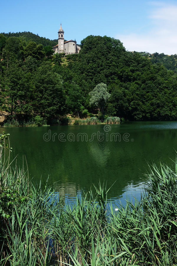 A church with its bell tower on the lake of Castel dell`Alpi stock images