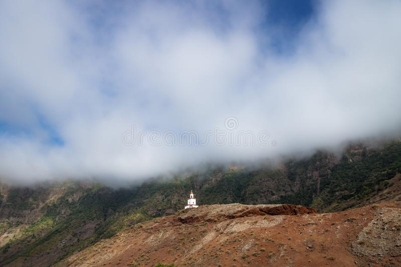 The church La Candelaria on a red hill with big cloud, Frontera, El Golfo, El Hierro, Canary Islands, Spain royalty free stock image