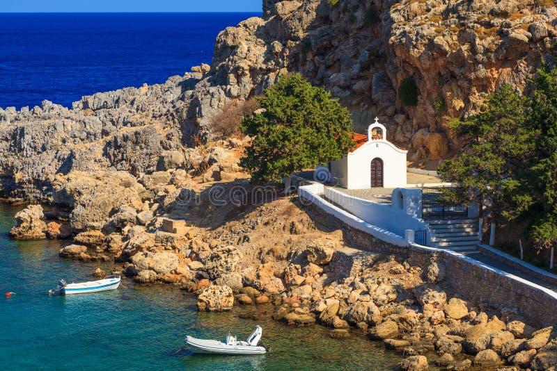 Church at Lindos Rhodes Greece. Tiny church and boats at St Pauls Bay Lindos Rhodes Greece Europe stock photo